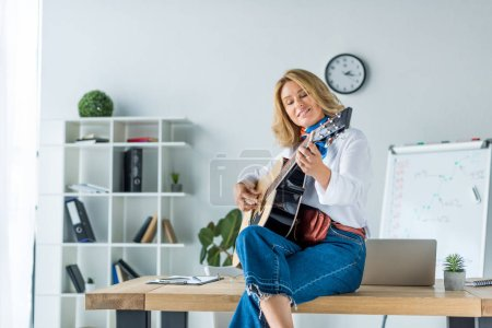 Photo for Smiling beautiful businesswoman playing acoustic guitar in office - Royalty Free Image