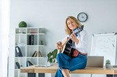 smiling beautiful businesswoman playing acoustic guitar in office
