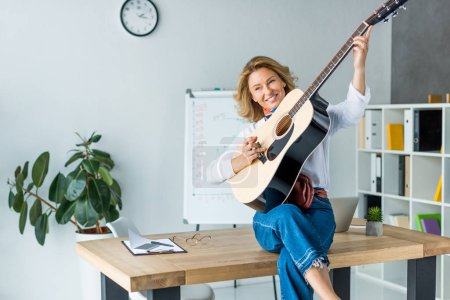 attractive businesswoman playing acoustic guitar in office