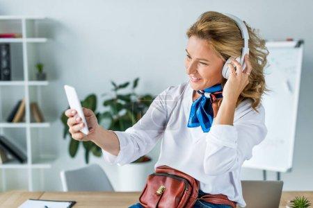Foto de Hermosa empresaria en auriculares que selfie con smartphone en oficina - Imagen libre de derechos