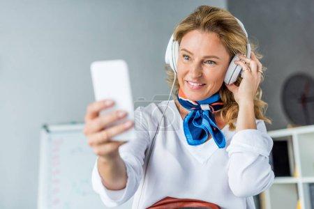 Photo pour Femme d'affaires attrayant dans les écouteurs prenant selfie smartphone au bureau - image libre de droit