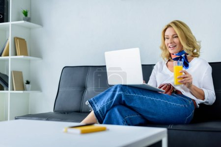 attractive businesswoman working with laptop in office and holding glass of juice