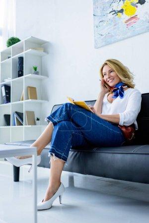 Photo pour Femme d'affaires attrayant, assis sur le canapé avec l'ordinateur portable au bureau - image libre de droit