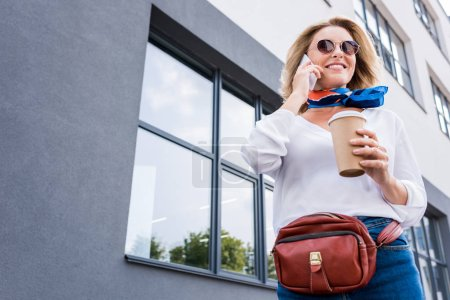 low angle view of attractive woman talking by smartphone on street
