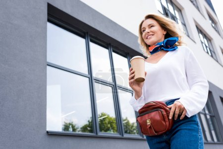 Photo for Low angle view of attractive woman walking with disposable coffee cup on street - Royalty Free Image