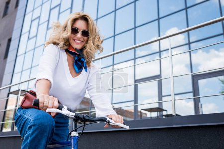 low angle view of attractive woman sitting on bike on street and looking at camera