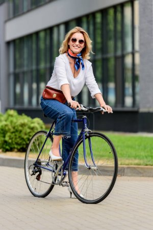 smiling attractive woman sitting on bike on street