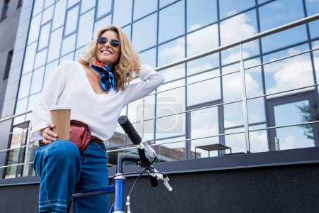 Photo pour Vue faible angle de jolie femme assis sur le vélo et la tenue de café dans la tasse de papier sur la rue - image libre de droit