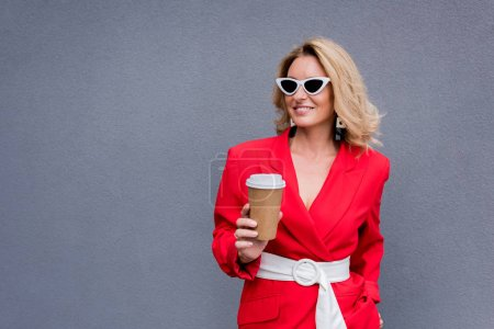 Photo for Smiling attractive woman in red jacket holding disposable coffee cup on street - Royalty Free Image