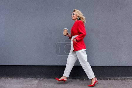 Photo for Side view of attractive woman in red jacket walking with coffee in paper cup on street - Royalty Free Image