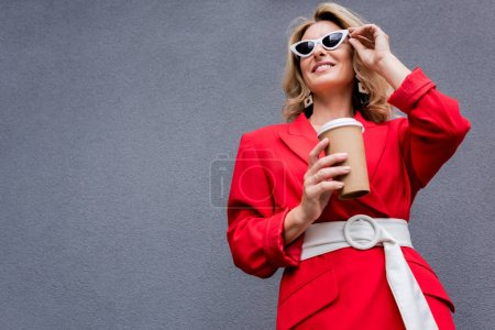 attractive woman in red jacket holding coffee in paper cup and touching sunglasses on street