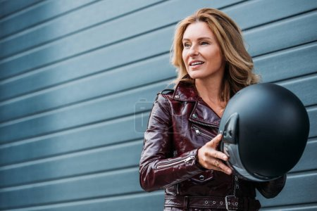 Photo for Attractive woman in leather jacket holding motorcycle helmet on street and looking away - Royalty Free Image
