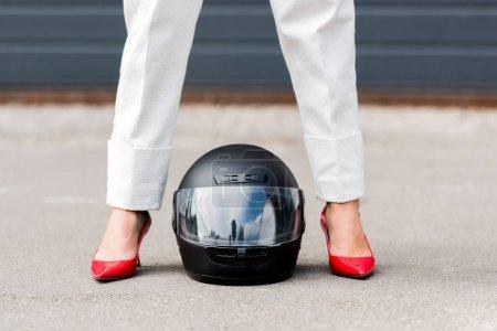 Photo pour Image recadrée de la femme en chaussures rouges debout près du casque de moto sur la rue - image libre de droit