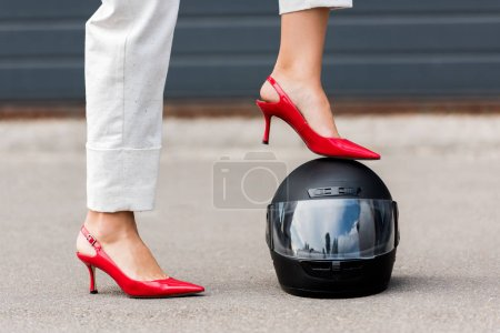 cropped image of woman in red high heels putting leg on motorcycle helmet on street