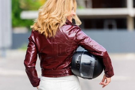 back view of woman in leather jacket holding motorcycle helmet on street