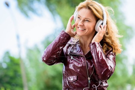 smiling attractive woman in leather jacket listening music on street