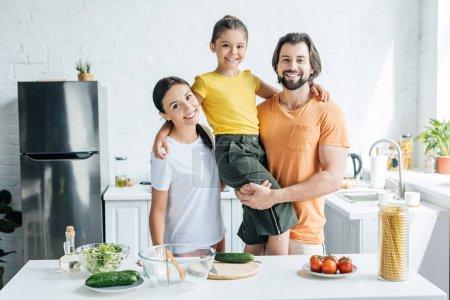 beautiful young family embracing at kitchen and looking at camera