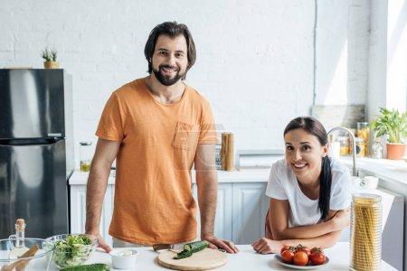 beautiful adult couple looking at camera while preparing salad together at kitchen