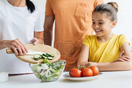 cropped shot of young family preparing salad at kitchen