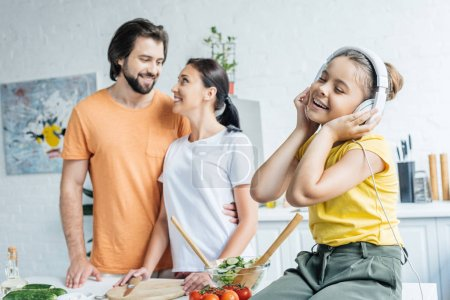 smiling little girl in headphones sitting on table while her parents embracing on background at kitchen