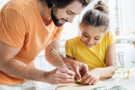 father and daughter carving cucumber while cooking at home together