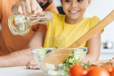 father and daughter pouring olive oil into bowl with salad