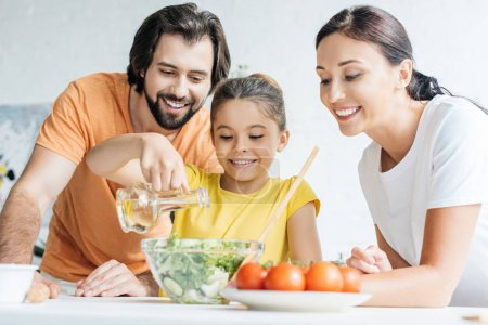beautiful young family preparing salad together at kitchen