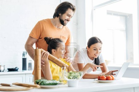 Photo for Beautiful young family using laptop while cooking at kitchen - Royalty Free Image