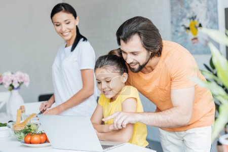 Photo for Beautiful young family using laptop together at kitchen - Royalty Free Image