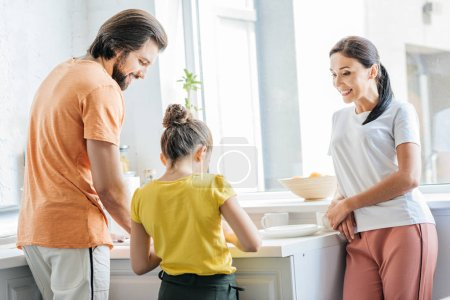 attractive young family washing dishes together at kitchen