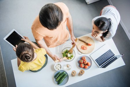 Photo for High angle view of young family with gadgets cooking together at kitchen - Royalty Free Image