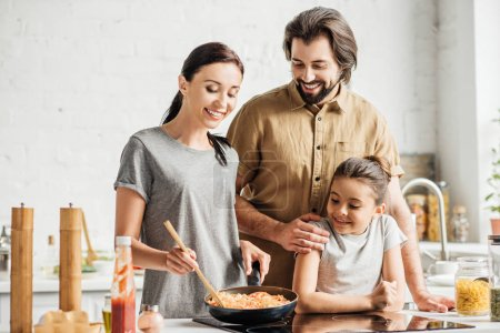 beautiful family with little daughter cooking omelet at kitchen