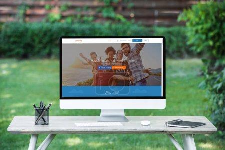 Foto de Enfoque selectivo del ordenador con la Página Web de couchsurfing en mesa al aire libre - Imagen libre de derechos