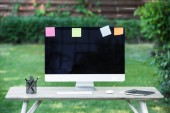 selective focus of computer monitor with blank screen and stick it notes at table outdoors
