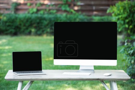 selective focus of laptop and computer with blank screens at table outdoors