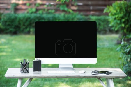 Photo for Selective focus of flask, textbook, smartphone and computer with blank screen on table outdoors - Royalty Free Image