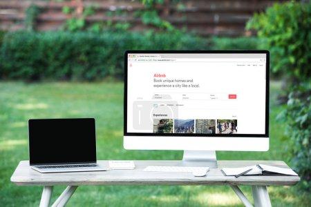 Photo pour Mise au point sélective d'ordinateur portable avec ordinateur écran blanc avec le site airbnb à table à l'extérieur - image libre de droit