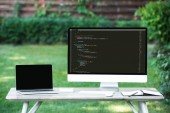 selective focus of laptop with blank screen and computer with programming language code at table outdoors