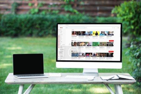 Foto de Enfoque selectivo del portátil con la computadora de la pantalla en blanco con el sitio web youtube en mesa al aire libre - Imagen libre de derechos