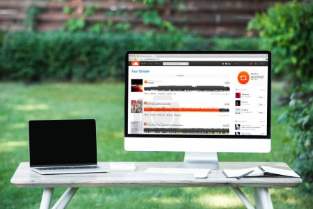 selective focus of laptop with blank screen computer with soundcloud website at table outdoors