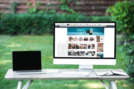 Photo pour Mise au point sélective d'ordinateur portable avec ordinateur écran blanc avec le site d'amazon à table à l'extérieur - image libre de droit