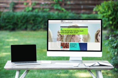 Photo pour Mise au point sélective d'ordinateur portable avec ordinateur écran blanc avec le site de science de bbc à table à l'extérieur - image libre de droit