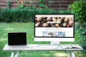 selective focus of laptop with blank screen computer with depositphotos.com website at table outdoors
