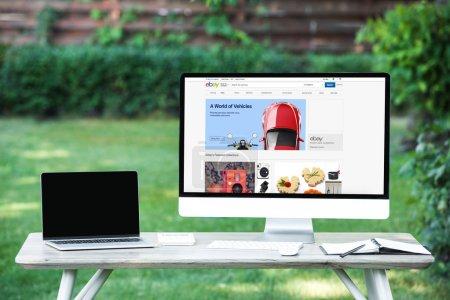 Photo pour Mise au point sélective d'ordinateur portable avec ordinateur écran blanc avec le site ebay à table à l'extérieur - image libre de droit