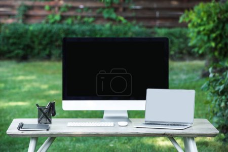 Photo for Selective focus of textbook, laptop and computer with blank screens at table outdoors - Royalty Free Image