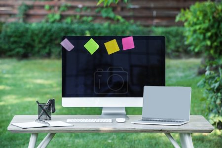 Photo for Selective focus of textbook, laptop and computer with blank screens and stick it notes at table outdoors - Royalty Free Image
