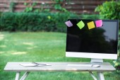 selective focus of textbook and computer with colorful stick it notes on table outdoors