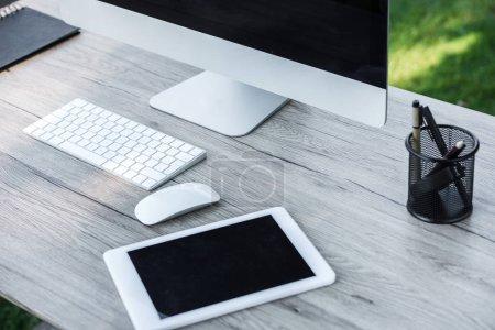 Foto de Enfoque selectivo de la tableta digital y un ordenador con pantallas en blanco en la mesa al aire libre - Imagen libre de derechos