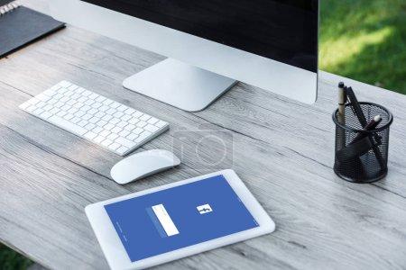 Foto de Enfoque selectivo de la tableta digital con el sitio web de facebook y un ordenador con pantalla en blanco en la mesa al aire libre - Imagen libre de derechos