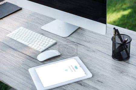 Foto de Enfoque selectivo de la tableta digital con el sitio web de Skype y un ordenador con pantalla en blanco en la mesa al aire libre - Imagen libre de derechos